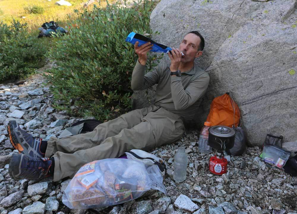 Alan enjoys dinner along the shore of Golden Lake before the climb to Hay Pass.